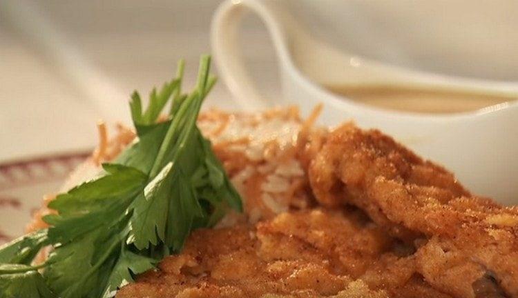 Отбивные из свинины. приготовленные на сковороде, подаем с гарниром из риса с лапшой и соусом.