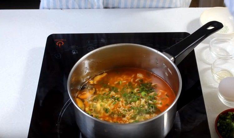 Добавляем в суп измельченный зеленый лук.