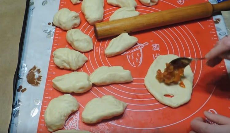 растягиваем порции теста в лепешки, делаем с одной сторон лепешки надрез.