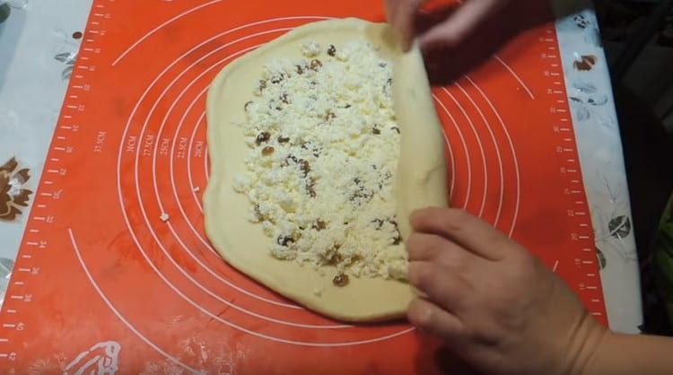 оставшееся тесто раскатываем, выкладываем на него творожную начинку.