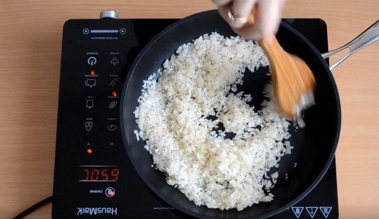 Помешивая, жарим рис с луком.