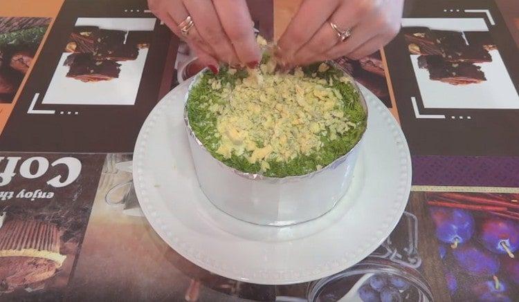 Украшаем середину салата измельченными яичными желтками.