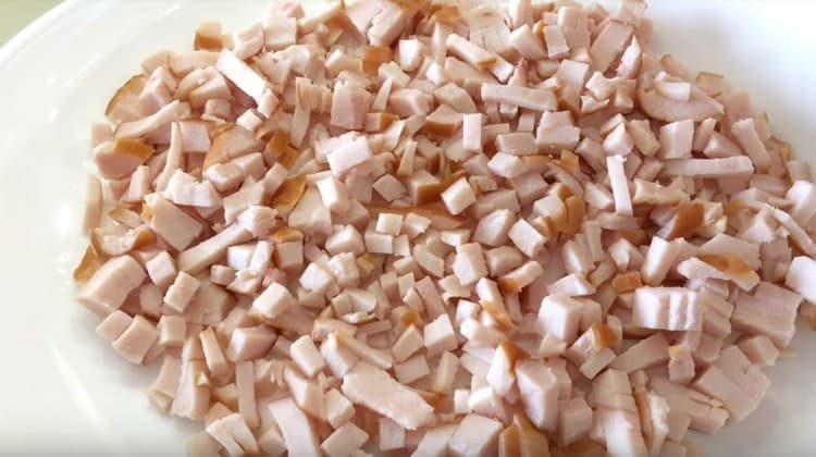 Копченую грудку нарезаем кубиком и выкладываем на блюдо.