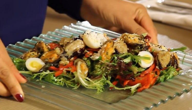 Готовый салат с мидиями посыпаем кунжутом.