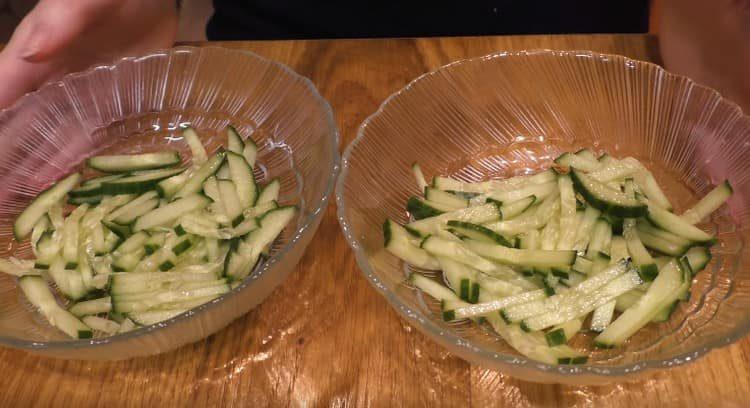 Первым слоем салата выкладываем огурцы.