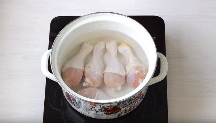 В кастрюлю выкладываем куриные голени, заливаем их водой.