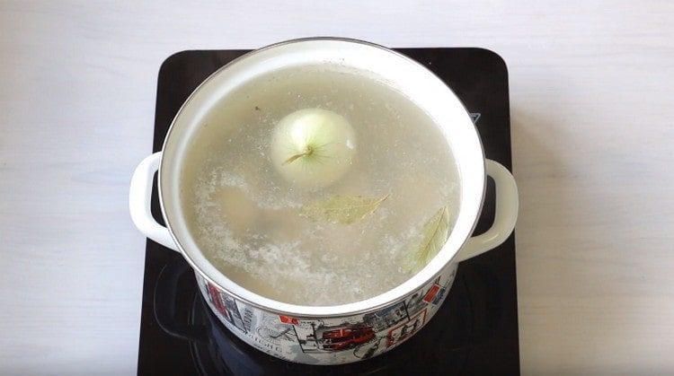 Добавляем в бульон луковицу, лавровый лист.