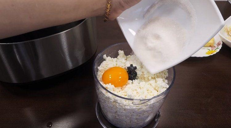 Творог выкладываем в чашу блендера, добавляем желток и сахар.