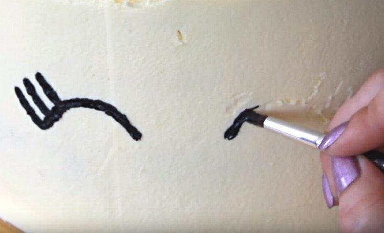 Черным пищевым красителем рисуем на торте глазки единорога.