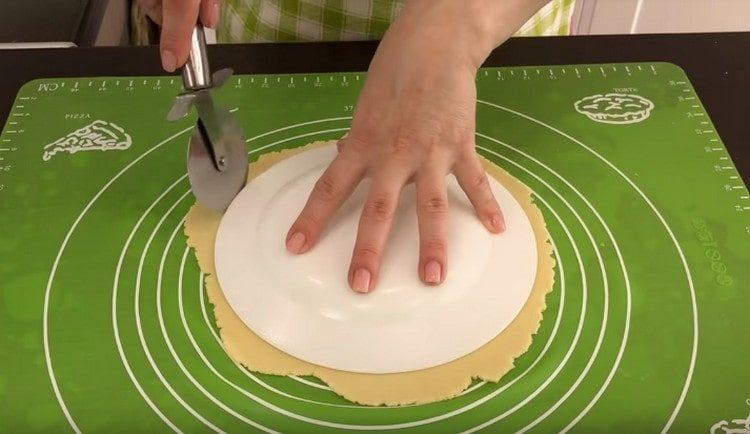 Вырезаем ровный круг при помощи тарелки.