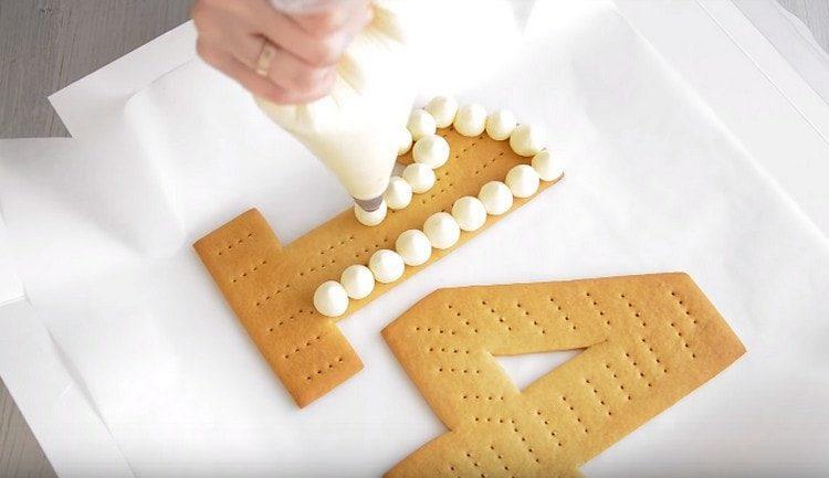 При помощи кондитерского мешка покрываем первую пару цифр каплями крема.