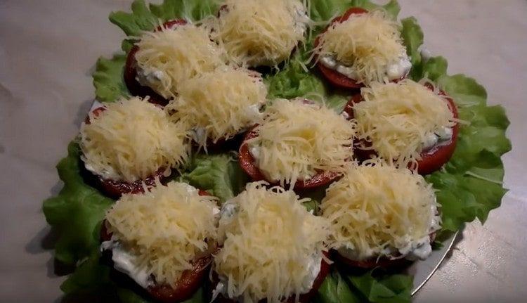 Посыпаем помидоры тертым сыром.