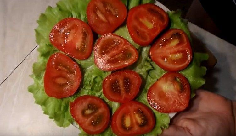 Помидоры нарезаем кружочками и выкладываем на листья салата.