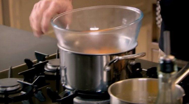 В миску выкладываем яичные желтки, добавляем к ним винный уксус и ставим все на водяную баню.