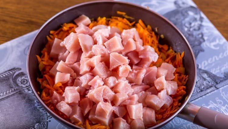 Нарезаем кусочками куриное филе и добавляем к овощам.