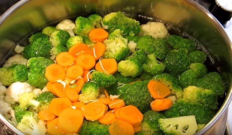 В кипящую воду выкладываем морковь и капусту.