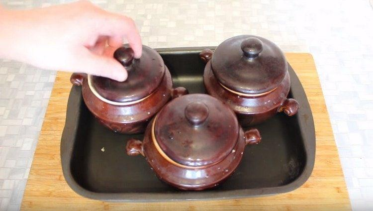 Накрываем горшочки крышками, ставим на противень и отправляем в духовку.