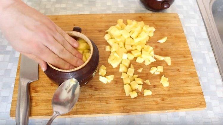 Картофель нарезаем кубиком и закладываем в горшочки поверх мяса.