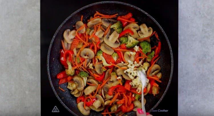 Приправляем грибы с овощами чесноком.