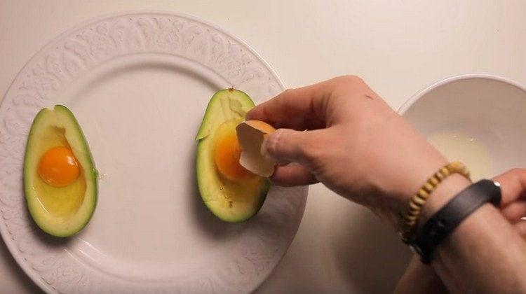 В каждую половину фрукта выбиваем яйцо.