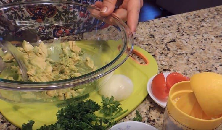 Вилкой разминаем мякоть авокадо.