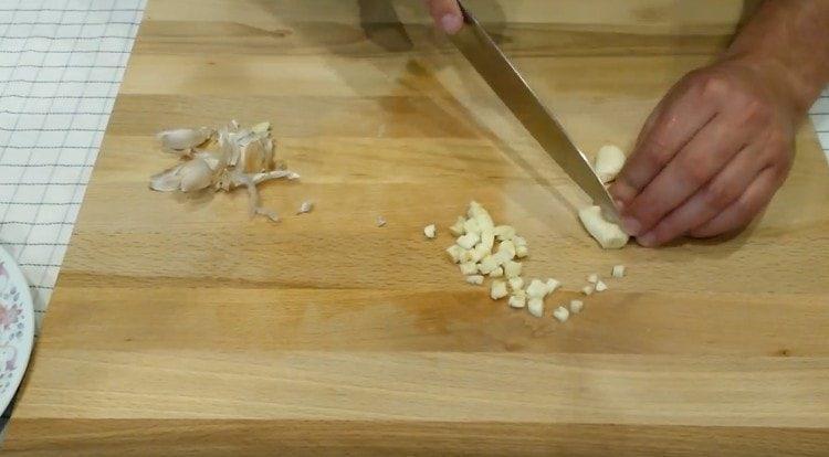 Измельчаем несколько зубчиков чеснока.