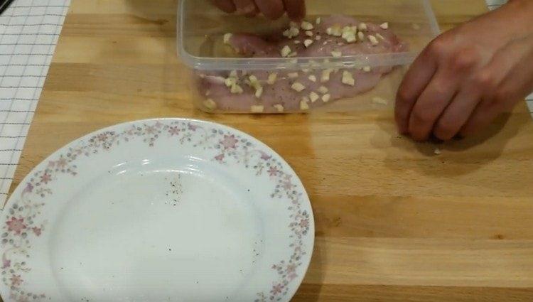 Выкладываем мясо индейки в пищевой контейнер, посыпаем чесноком