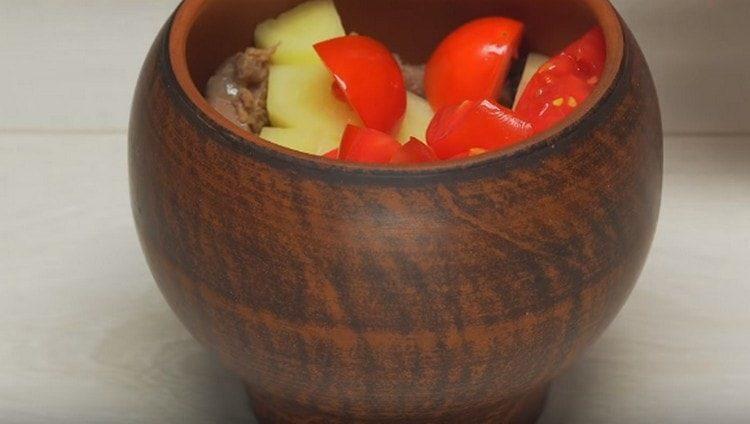 На дно горшочка для запекания выкладываем соус, измельченную кинзу, мясо, картофель и помидоры.