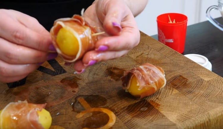 Картофель скрепляем с беконом при помощи зубочисток.