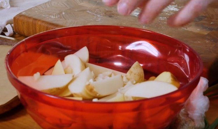 Выкладываем картошку в миску, добавляем к нему измельченный чеснок.