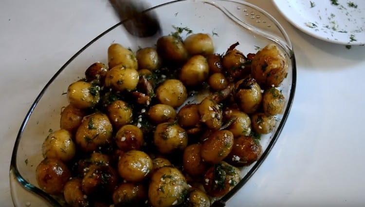 Готовую картошку с грудинкой, запеченную в духовке, поливаем чесночной заправкой и перемешиваем.