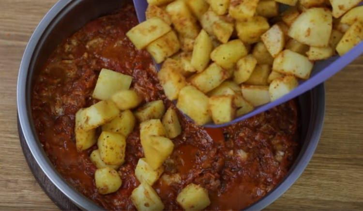 Добавляем картофель на сковороду к тушенке и овощам.