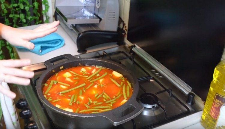 Добавляем картошку с фасолью в казан, заливаем воду, добавляем соль, перец горошком и тушим блюдо.