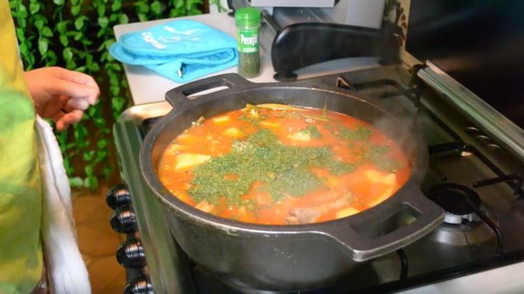 В практически готовое блюдо добавляем измельченный чеснок и зелень.