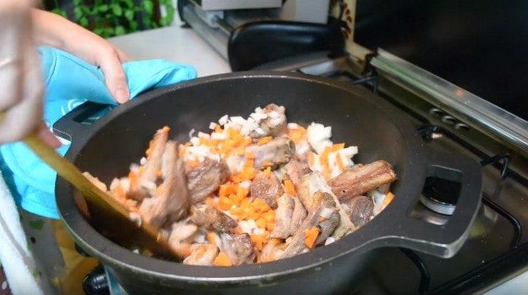 Морковь с луком добавляем в казан к ребрышкам.