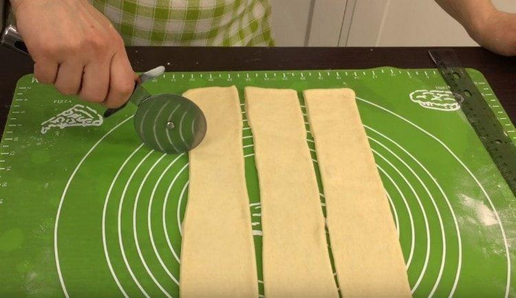 Разрезаем получившийся пласт теста на полоски.