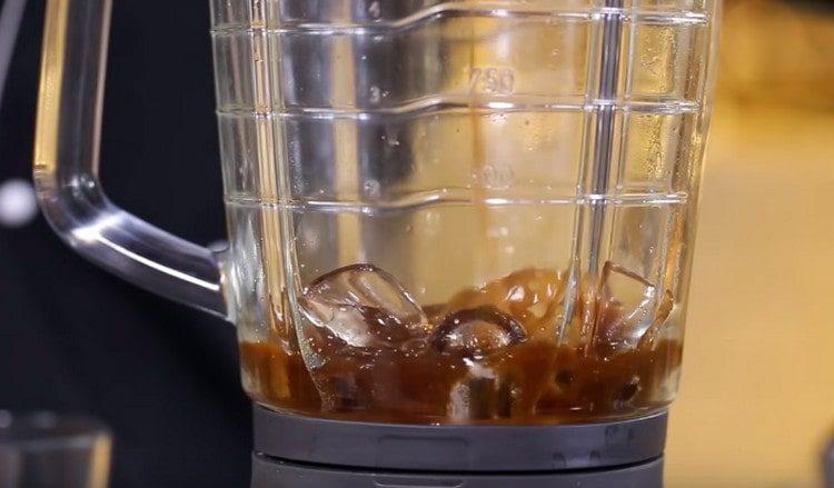 В стакан блендера наливаем предварительно заваренный кофе. добавляем кубики льда и сахар