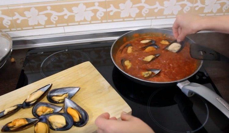 Выкладываем мидии в томатный соус и тушим еще несколько минут под крышкой.