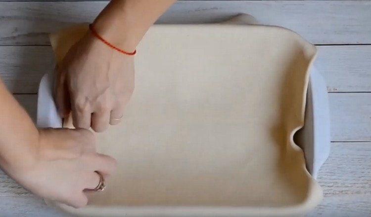 Тонко раскатываем тесто и выкладываем его в смазанную маслом форму.