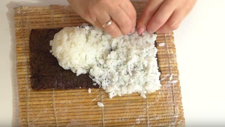 на лист нори выкладываем рис и равномерно распределяем.
