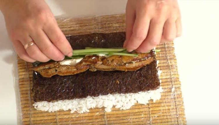 Переворачиваем лист нори рисом вниз и выкладываем на него курицу, огурцы, перья зеленого лука, а также сливочный сыр.