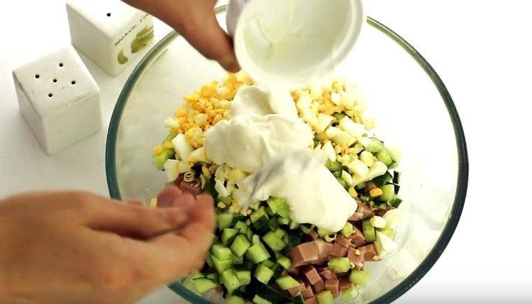 Соединяем все подготовленные ингредиенты и заправляем салат майонезом.