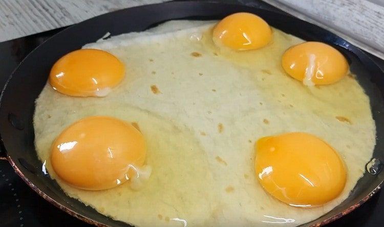 Выбиваем на лаваш яйца.