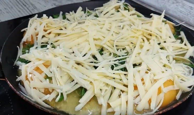 Сразу присыпаем яйца зеленью и тертым сыром.